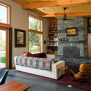 Example of a mountain style open concept black floor living room design in Other with beige walls, a standard fireplace, a stone fireplace and a concealed tv