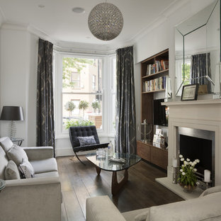 Small traditional formal enclosed living room in London with white walls, dark hardwood flooring, a standard fireplace, a metal fireplace surround and a wall mounted tv.
