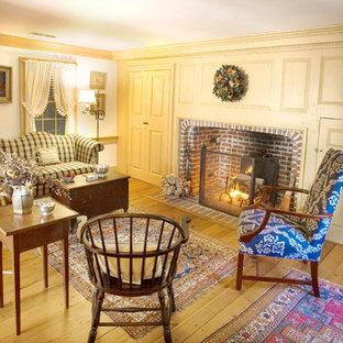 Foto di un piccolo soggiorno classico chiuso con pareti gialle, pavimento in legno massello medio, camino classico, cornice del camino in mattoni e sala formale
