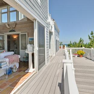 Idee per un grande soggiorno stile marino aperto con pavimento in terracotta, nessun camino, nessuna TV, angolo bar e pareti beige