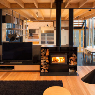 Inspiration for a contemporary open concept medium tone wood floor living room remodel in Auckland with a music area, a tv stand and a wood stove