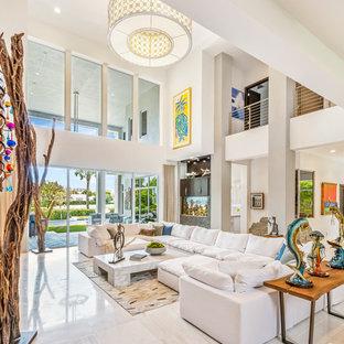 Bild på ett stort tropiskt allrum med öppen planlösning, med vita väggar, vitt golv, marmorgolv, en standard öppen spis och en spiselkrans i metall