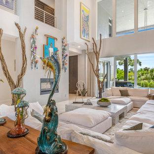 Modelo de salón para visitas abierto, tropical, grande, con suelo de mármol, chimenea tradicional, marco de chimenea de metal, paredes blancas y suelo blanco