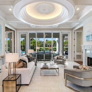 マイアミの地中海スタイルのおしゃれな独立型リビング (フォーマル、ベージュの壁、横長型暖炉、石材の暖炉まわり、テレビなし、ベージュの床) の写真
