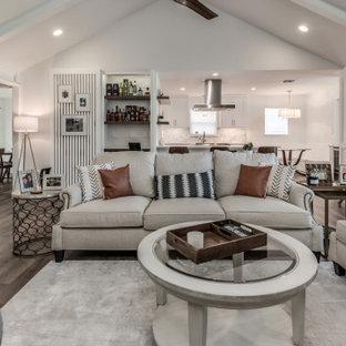 ヒューストンの中サイズのビーチスタイルのおしゃれなリビング (白い壁、磁器タイルの床、標準型暖炉、レンガの暖炉まわり、据え置き型テレビ、白い床) の写真
