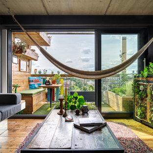 Diseño de salón cerrado, industrial, pequeño, con suelo de madera en tonos medios, pared multimedia, paredes grises y suelo marrón