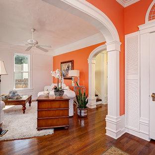 Foto de salón cerrado, clásico, pequeño, con parades naranjas y suelo de madera en tonos medios