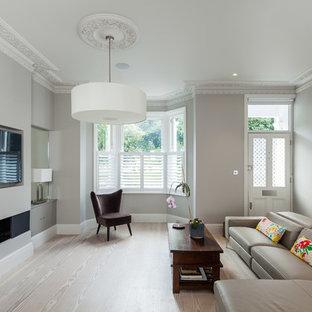 Modelo de salón para visitas cerrado, contemporáneo, con paredes grises, suelo de madera clara, chimenea lineal y televisor colgado en la pared