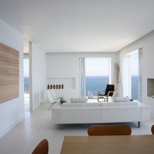 Esempio di un piccolo soggiorno minimalista aperto con pareti bianche, camino classico, nessuna TV, pavimento in pietra calcarea, pavimento bianco e cornice del camino in pietra