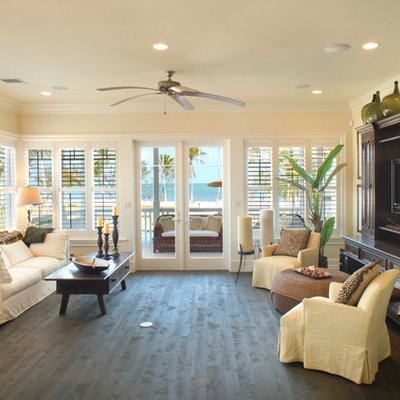 Example of a large island style open concept dark wood floor and brown floor living room design in Miami with beige walls and a concealed tv