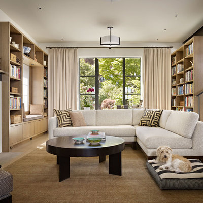 Living room library - contemporary light wood floor living room library idea in Seattle with white walls and a standard fireplace