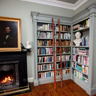 Inspiration for a mid-sized traditional enclosed living room in Cork with a library, grey walls, dark hardwood floors, a standard fireplace and a wood fireplace surround.