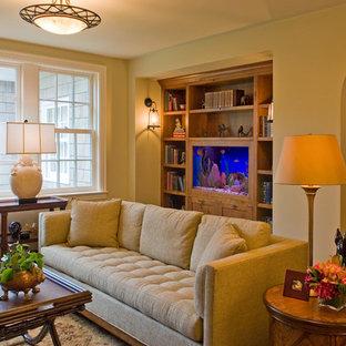 Ispirazione per un soggiorno classico di medie dimensioni e chiuso con sala formale, pareti beige, pavimento in legno verniciato, camino bifacciale, cornice del camino in pietra e TV nascosta