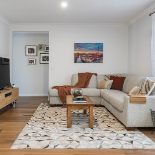 This is an example of a small transitional formal enclosed living room in Brisbane with white walls, medium hardwood floors, a freestanding tv and brown floor.