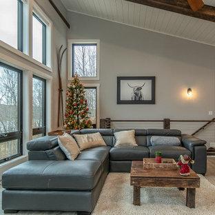 Modelo de salón abierto y machihembrado, minimalista, de tamaño medio, con paredes grises, suelo de madera clara, chimenea de esquina, marco de chimenea de piedra, televisor colgado en la pared y suelo marrón
