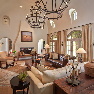Inspiration for a mid-sized mediterranean formal and enclosed terra-cotta tile and red floor living room remodel in Houston with a two-sided fireplace, beige walls, a plaster fireplace and no tv