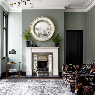 Medium sized classic living room in London with green walls, medium hardwood flooring, a standard fireplace, a stone fireplace surround and brown floors.