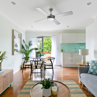 Mid-sized beach style formal open concept living room in Sydney with white walls, medium hardwood floors and brown floor.