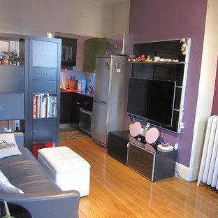 Imagen de salón abierto, moderno, pequeño, sin chimenea, con paredes púrpuras, suelo de madera clara y televisor colgado en la pared