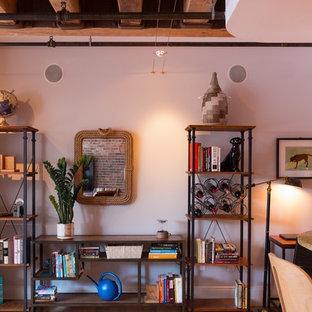 Imagen de salón abierto, industrial, de tamaño medio, sin chimenea, con paredes marrones, suelo de madera clara, televisor colgado en la pared y suelo beige