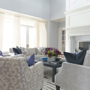Large transitional formal and open concept medium tone wood floor living room photo in Boston with blue walls, a two-sided fireplace, a stone fireplace and no tv