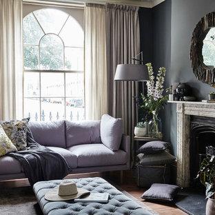 Imagen de salón tradicional, de tamaño medio, con paredes grises, suelo de madera en tonos medios, chimenea tradicional, suelo marrón y marco de chimenea de piedra