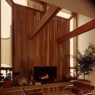 デンバーの大きいモダンスタイルのおしゃれなリビングロフト (ベージュの壁、淡色無垢フローリング、標準型暖炉、木材の暖炉まわり) の写真