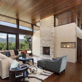 Свежая идея для дизайна: открытая гостиная комната в современном стиле с полом из бамбука, стандартным камином, фасадом камина из камня и бежевыми стенами - отличное фото интерьера