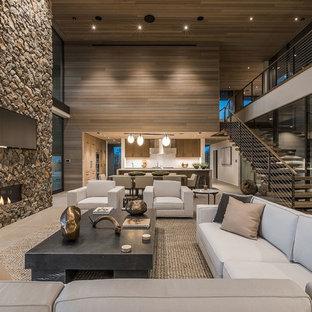 Foto de salón abierto, actual, extra grande, con paredes marrones, chimenea de esquina, marco de chimenea de piedra, televisor colgado en la pared y suelo beige