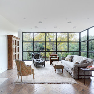 Large trendy open concept medium tone wood floor living room photo in Austin with white walls, a standard fireplace, a plaster fireplace and no tv