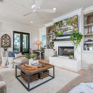 Offenes Wohnzimmer mit weißer Wandfarbe, Backsteinboden, Kamin, Kaminumrandung aus Backstein, Wand-TV und rotem Boden in Sonstige