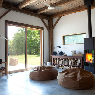 Example of a large mountain style open concept concrete floor and gray floor living room design in New York with a wood stove, white walls, a metal fireplace and no tv