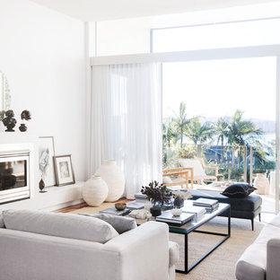 Aménagement d'un salon bord de mer de taille moyenne et ouvert avec un mur blanc, un sol en bois foncé, une cheminée standard et un sol marron.