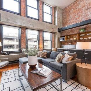 Idee per un soggiorno industriale aperto con pareti rosse e pavimento in legno massello medio
