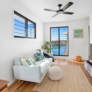 Design ideas for a mid-sized tropical open concept living room in Gold Coast - Tweed with white walls, medium hardwood floors, a freestanding tv and brown floor.