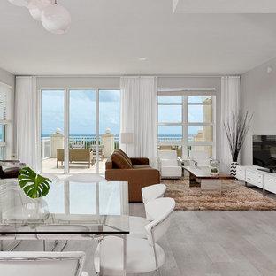 Foto di un soggiorno contemporaneo aperto con parquet chiaro, pareti grigie, nessun camino, TV autoportante e pavimento grigio