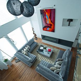 他の地域の巨大なコンテンポラリースタイルのおしゃれなリビングロフト (白い壁、無垢フローリング、横長型暖炉、タイルの暖炉まわり、内蔵型テレビ、茶色い床) の写真
