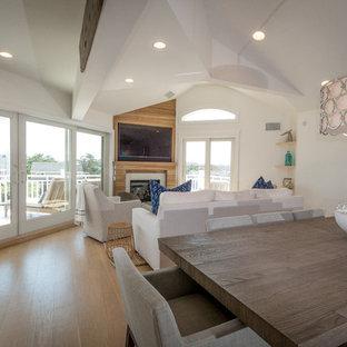 ニューヨークの大きいビーチスタイルのおしゃれなLDK (白い壁、淡色無垢フローリング、コーナー設置型暖炉、木材の暖炉まわり、壁掛け型テレビ) の写真