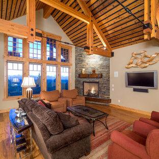 Cette photo montre un salon montagne avec un mur beige, une cheminée d'angle et un téléviseur fixé au mur.
