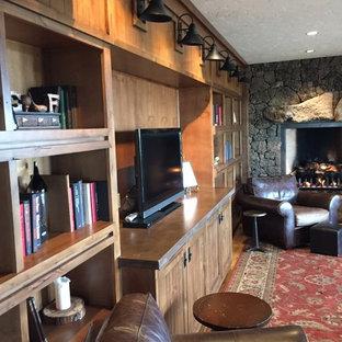 Ejemplo de salón cerrado, rural, grande, con paredes marrones, suelo de madera en tonos medios, chimenea tradicional, marco de chimenea de piedra y pared multimedia