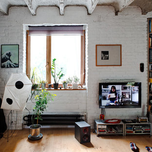 Urban medium tone wood floor living room photo with white walls and a wall-mounted tv