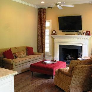 シャーロットの中サイズのトランジショナルスタイルのおしゃれなLDK (標準型暖炉、ライブラリー、ベージュの壁、無垢フローリング、木材の暖炉まわり、壁掛け型テレビ) の写真