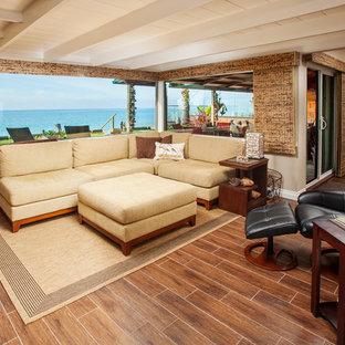 オレンジカウンティの巨大なビーチスタイルのおしゃれなLDK (ベージュの壁、磁器タイルの床、据え置き型テレビ、フォーマル、標準型暖炉、木材の暖炉まわり、茶色い床) の写真