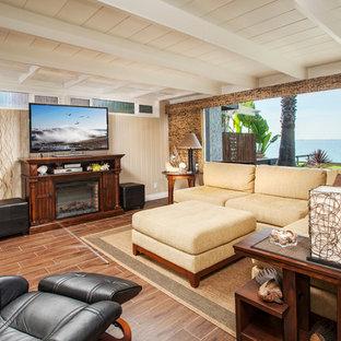 オレンジカウンティの巨大なトロピカルスタイルのおしゃれなLDK (ベージュの壁、磁器タイルの床、標準型暖炉、据え置き型テレビ、木材の暖炉まわり、茶色い床) の写真