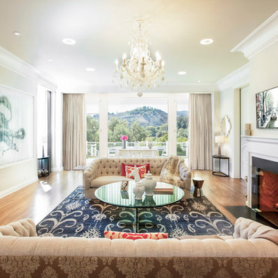 Living room - transitional medium tone wood floor living room idea in Los Angeles with beige walls and a standard fireplace