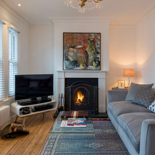 This is an example of a traditional formal enclosed living room in London with white walls, medium hardwood flooring, a standard fireplace, a freestanding tv and brown floors.