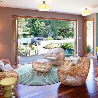Foto de salón para visitas abierto, contemporáneo, de tamaño medio, sin chimenea y televisor, con paredes púrpuras, suelo de madera en tonos medios y suelo marrón