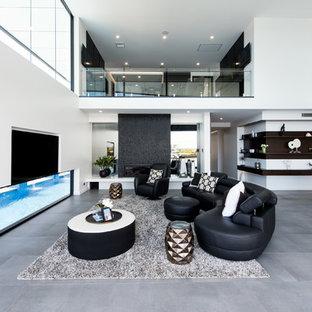 ゴールドコーストのコンテンポラリースタイルのおしゃれなLDK (白い壁、標準型暖炉、石材の暖炉まわり、壁掛け型テレビ、グレーの床) の写真