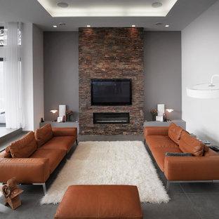 Idee per un soggiorno classico di medie dimensioni e aperto con pareti grigie, camino classico, cornice del camino in pietra, TV a parete, pavimento in ardesia e pavimento grigio