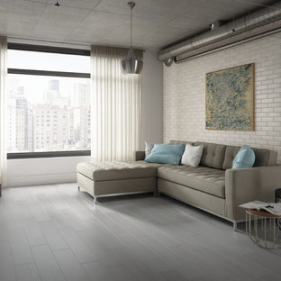 Living room - large industrial open concept porcelain floor living room idea in Boise with white walls and a media wall